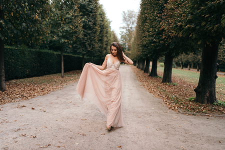Young beautiful woman in long rose evening dress walking path in park. Fashion style portrait of gorgeous beautiful girl outdoors Imagens