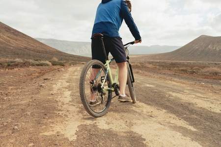 Close up, a wheel of mountain bike in mountains with rider wearing casual cloth