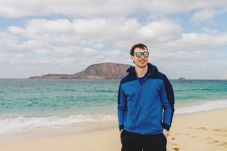 Handsome man in glasses and blue sport jacket on the beach