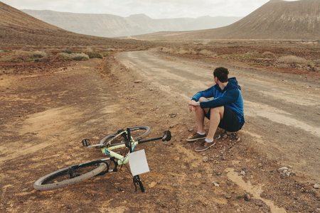 Handsome man in casual outfit sitting near of mountain bike on the road , Canarian island Imagens