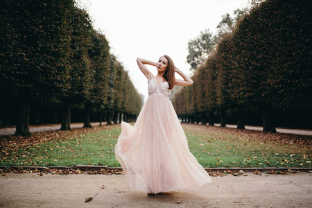 Portrait of beautiful brunette  in long chiffon rose dress standing in park