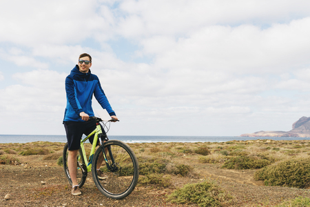 Handsome man in casual outfit ride a mountain bike on Canarian island