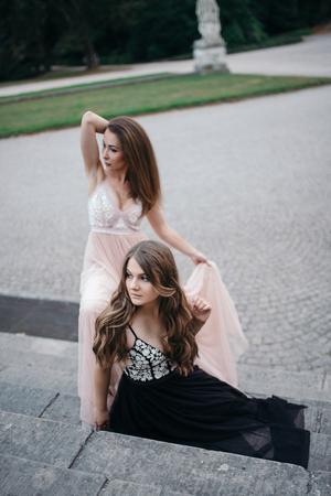 Portrait of two beautiful brunettes in long chiffon dresses standing and sitting at a park