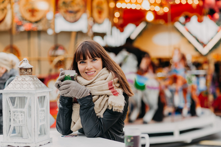 beautiful woman in scarf drinks mulled wine on christmas market