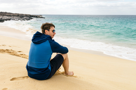 man looks at ocean sitting on the sand at paradise beach Imagens