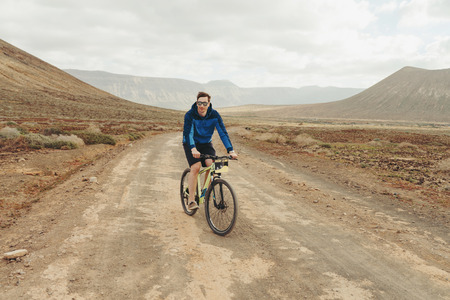 handsome man in casual outfit riding a mountain bike with â € ¢ rent a bikeâ € writting on it in mountains