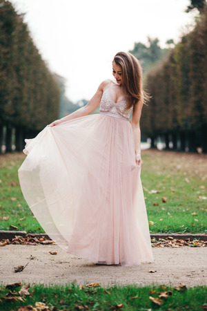 Portrait of young beautiful brunette  in long chiffon pink dress standing in park