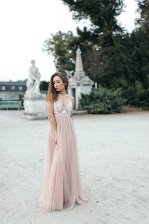 Beautiful woman in long rose evening dress walking path in park. Fashion style portrait of gorgeous beautiful girl outdoors