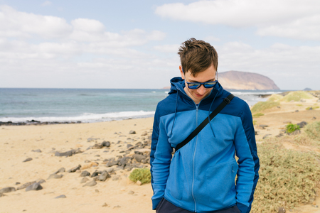 handsome man in glasses and blue sport  jacket on the beach Imagens