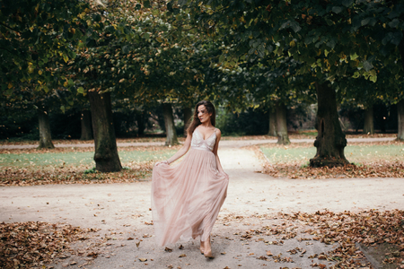 Young beautiful woman in long  rose  evening dress walking path in park. Fashion style portrait of gorgeous beautiful girl outdoors