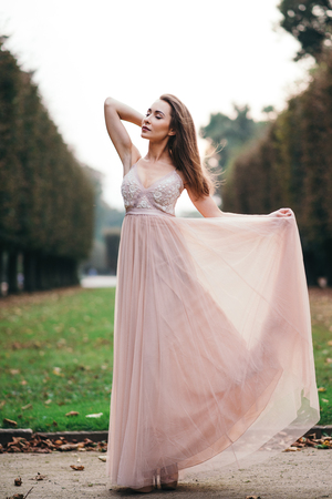 Portrait of young beautiful brunette in long chiffon pink dress standing in park Imagens