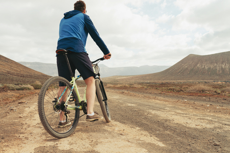 close up, a wheel of mountain bike in mountains with rider in casual clouth