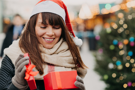 beautiful brunette woman in santa hat holding present box on christmas market