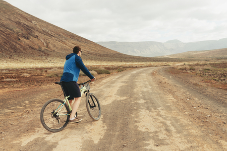 handsome man  in casual outfit ride a mountain bike in mountains, back view