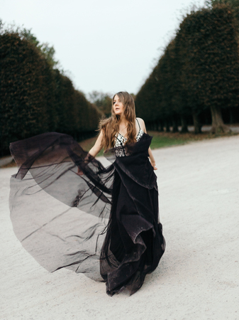 Young beautiful woman in long black  evening dress walking path in park. Fashion style portrait of gorgeous beautiful girl outdoors Imagens