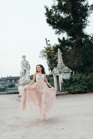 beautiful woman in long rose evening dress walking path in park . Fashion style portrait of gorgeous beautiful girl outdoors