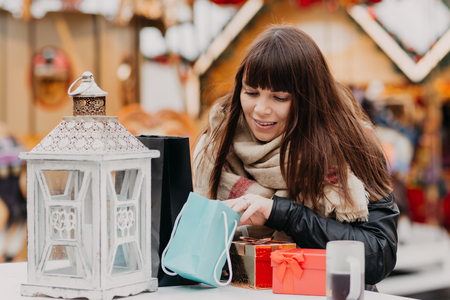 beautiful woman in scarf looking at her presents on christmas market