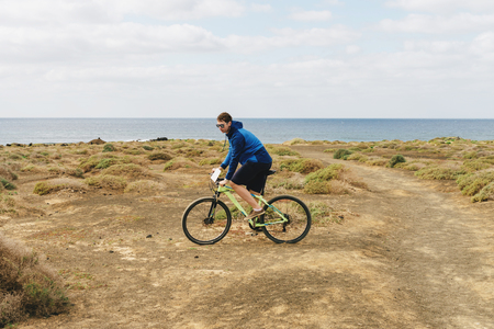 handsome man  in casual outfit ride a mountain bike on canarien  island