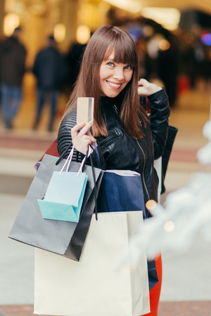 Christmas Shopping. Beautiful Happy woman With Credit Card In Shopping Street. Shopping Bags. Shopping Center. Christmas Sales Imagens