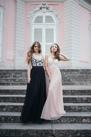 Portrait of two beautiful brunettes in long chiffon dresses standing on the background of the palace in the style of baroque outdoor
