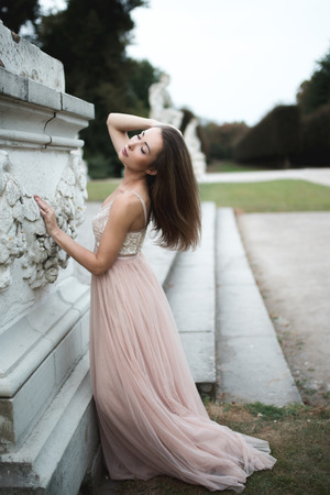 Fashion brunette model posing in rose long chiffon dress  by sculpture