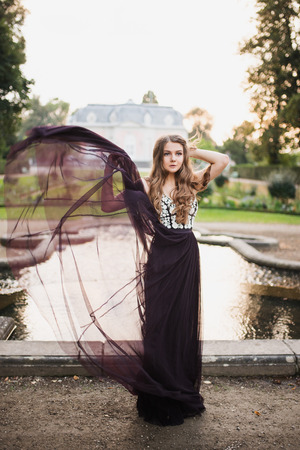 Portrait of beautiful young brunette  in long chiffon black dress standing on the background of the old palace in the style of baroque Imagens
