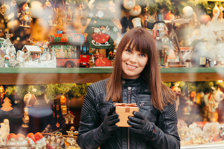 beautiful woman holding christmas present in front of christmas tree toys , outside Imagens