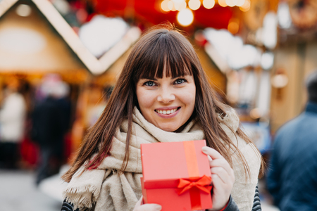 beautiful brunette woman  in scarf holding a present box on a christmas market Imagens