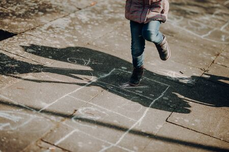adorable toddler girl playing hopscotch game outdoor, cold season Standard-Bild