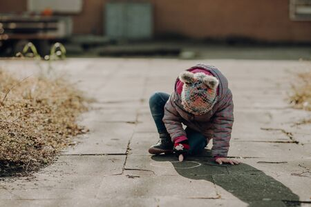 toddler girl painted on the asphalt with a chalk, outdoor, cold weather Standard-Bild