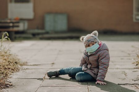 toddler girl in a facial mask painted on the asphalt with a chalk, playing alone outdoor, cold weather