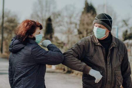 two seniors wearing facial masks and gloves greeting with hand sign, outdoor Standard-Bild
