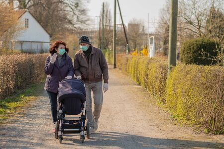 Grandparents in facial masks walking with baby in buggy during quarantine , outdoor