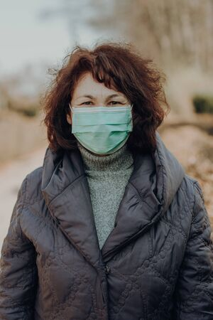 elderly woman wearing facial mask to prevention of infection, outdoor