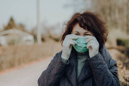 elderly woman wearing facial mask and gloves to prevention of infection, outdoor