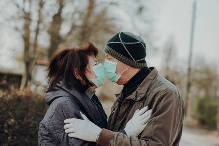 couple of two seniors kisses each other throught facial masks outdoor