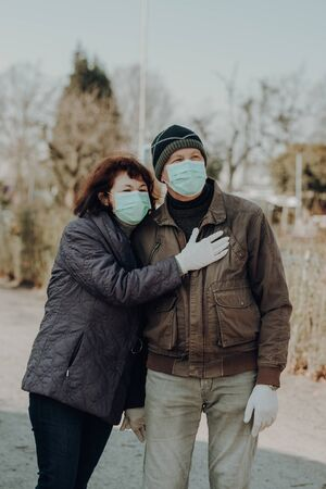 couple of two seniors wearing facial masks and gloves walking outside during infections danger
