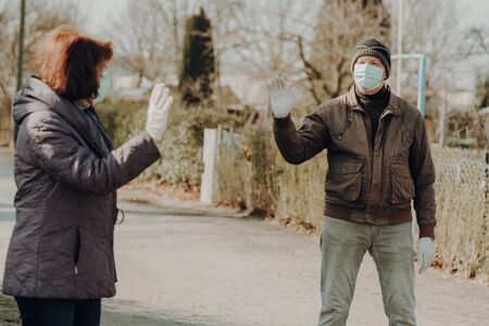 two seniors wearing facial masks and gloves waves by the appointment, outdoor Standard-Bild