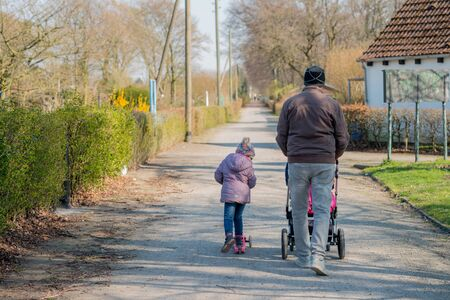 Grandfather walking with baby in buggy and toddler granddaughter, back view