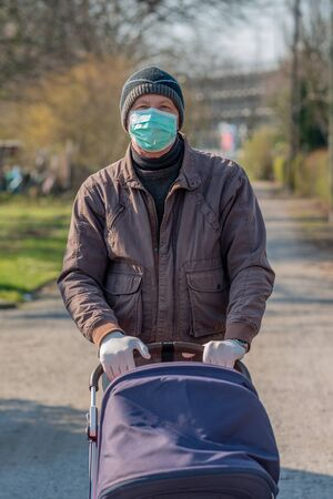 Grandfather in facial mask and gloves walking with baby in buggy, outdoor