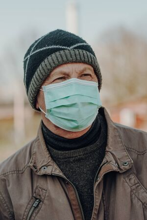 elderly man wearing facial mask to prevention of infection, outdoor Standard-Bild