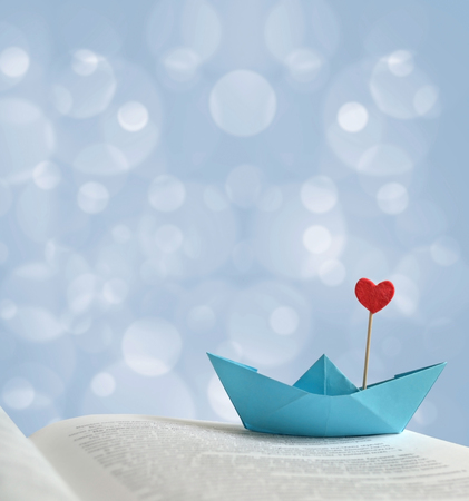 The photo blue paper boat with a red heart on the page of the book, there is space for text. Can be used as a template, romantic greeting card, poster for the design of your project