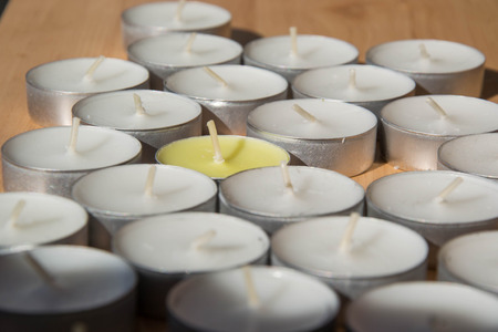 Bunch of white and yellow round candles on wooden board, brown wood background Stock fotó