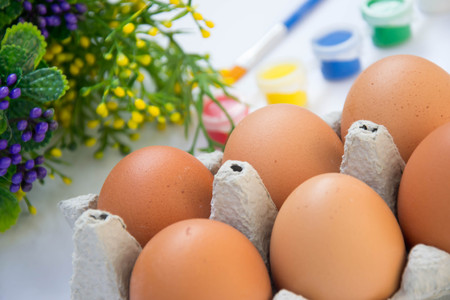 Easter brown chicken eggs in carton container, with plastic flowers and blurred paints, colorful palette on the background, paint equipment on white background Banco de Imagens