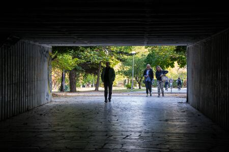 Varna, Bulgaria, 10/27, 2019 - People walking through a dark underpass with glowing end, underground passage, blurred people silhouettes