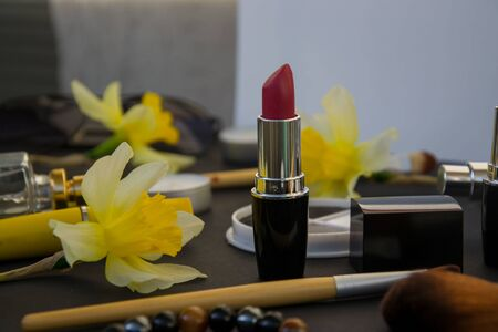 Beautiful yellow daffodils and set of decorative cosmetics, brushes and lipstick, jewelry, perfume, make up and girly stuff, selective focus