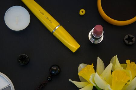 Beautiful yellow daffodils and set of decorative cosmetics, brushes and lipstick, jewelry, perfume, make up and girly stuff, flat lay, top view