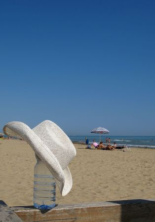 Water bottle covered by a straw hat at beach photo