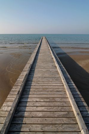 Wooden pier perspective on seashore photo