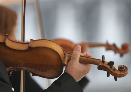Violin players on defocused background. Stock Photo